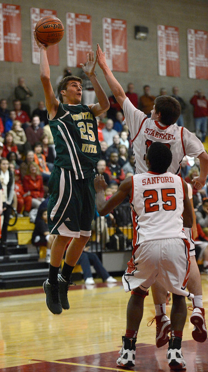 . LITTLETON, CO. - JANUARY 29: Mountain Vista Graham Smith (25) takes a shot over Regis Bryan Staerkel (13) during their game January 29, 2013 at Regis.  (Photo By John Leyba / The Denver Post)