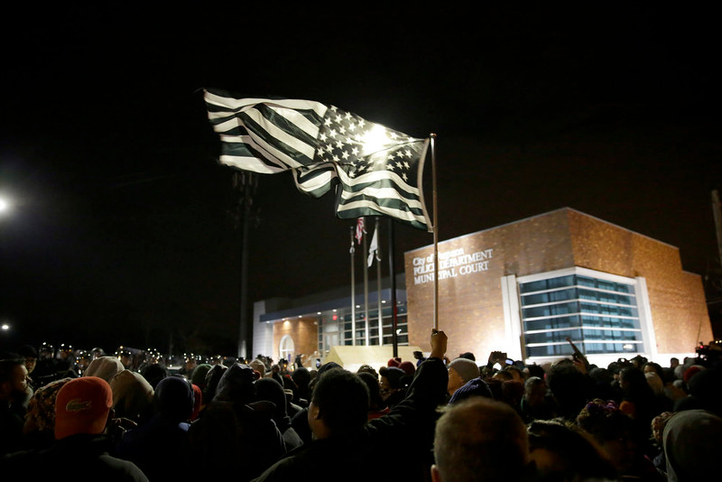 . A protester flies a black and white flag as many protesters gather in front of the Ferguson Police Department as they listen to the announcement of the grand jury decision Monday, Nov. 24, 2014, in Ferguson, Mo. A grand jury decided not to indict Ferguson police officer Darren Wilson in the death of Michael Brown, the unarmed, black 18-year-old whose fatal shooting sparked sometimes violent protests. (AP Photo/David Goldman)