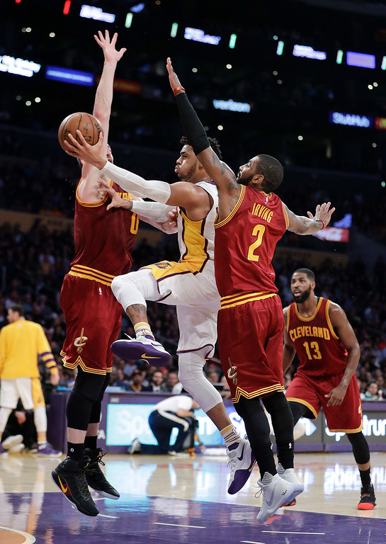 . Los Angeles Lakers\' D\'Angelo Russell, center, goes up for a basket under defense by Cleveland Cavaliers\' Kyrie Irving, right, and Kevin Love during the first half of an NBA basketball game Sunday, March 19, 2017, in Los Angeles. (AP Photo/Jae C. Hong)