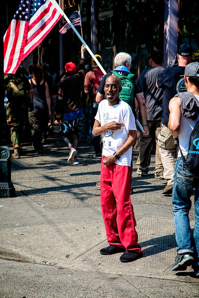"""A passerby in bright, red pants stands on the street corner while members of the """"Liberty or Death"""" rally march by."""