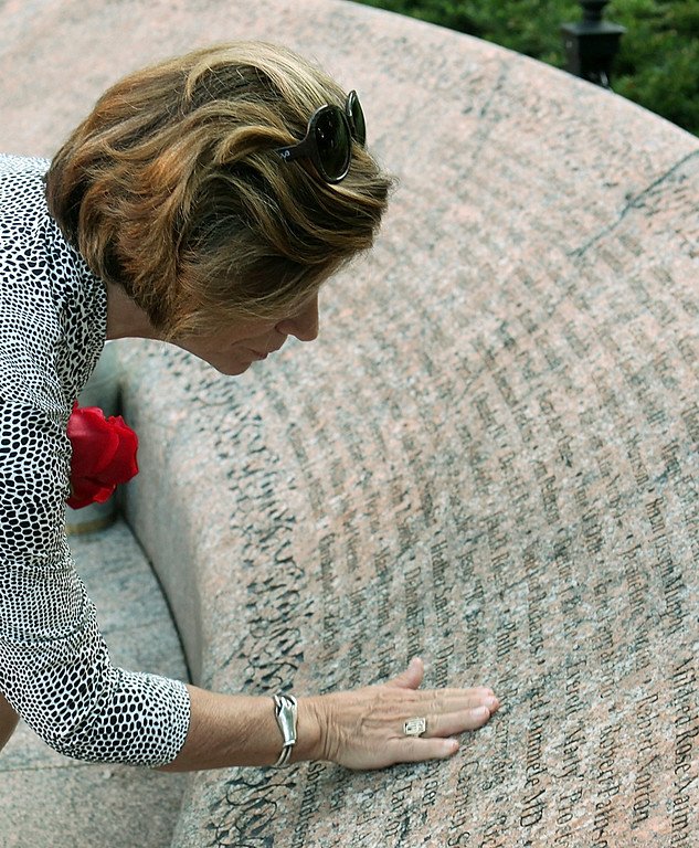 . Loreen Sellitto pauses Wednesday, Sept. 11, 2013, at the Garden of Remembrance Memorial in Boston Public Garden to honor her son, Matthew, who died in the 9/11 terror attacks in in New York. The two passenger jets that crashed into the World Trade Center in New York on Sept. 11, 2001 flew out of Logan International Airport in Boston. (AP Photo/Boston Herald, Angela Rowlings)
