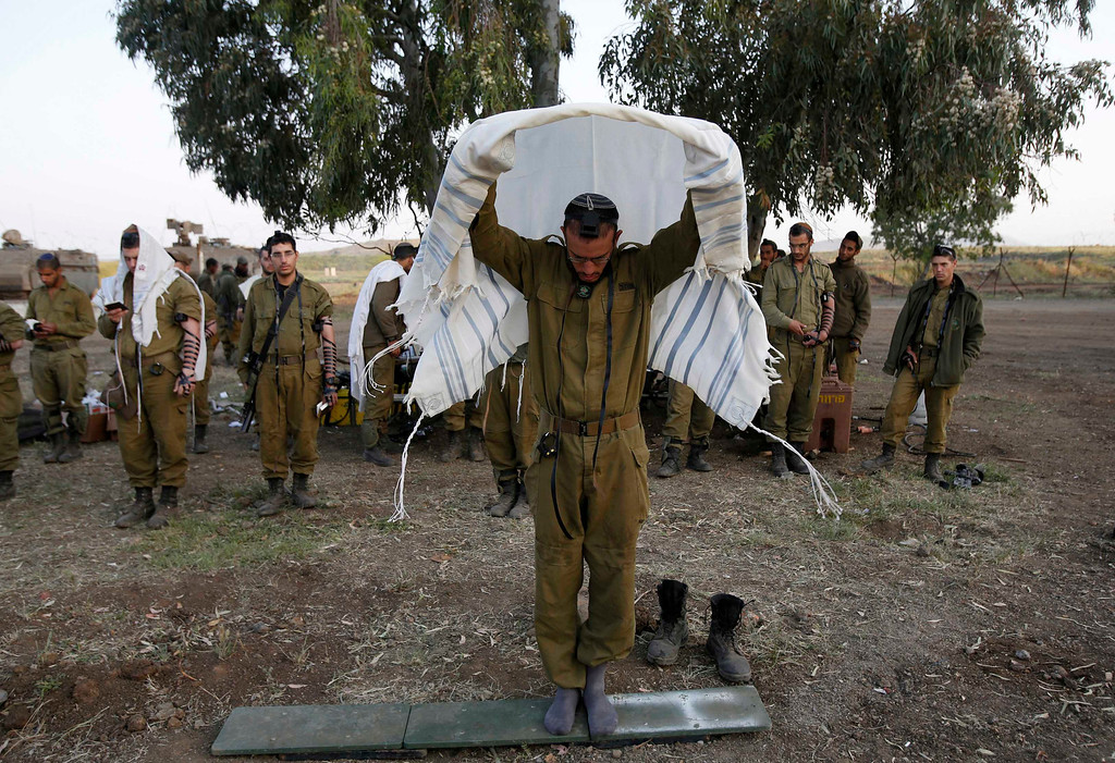 . Israeli soldiers from the Golani Brigade pray close to the ceasefire line between Israel and Syria on the Israeli occupied Golan Heights May 7, 2013. Israel played down weekend air strikes close to Damascus reported to have killed dozens of Syrian soldiers, saying they were not aimed at influencing its neighbour\'s civil war but only at stopping Iranian missiles reaching Lebanese Hezbollah militants. REUTERS/Baz Ratner