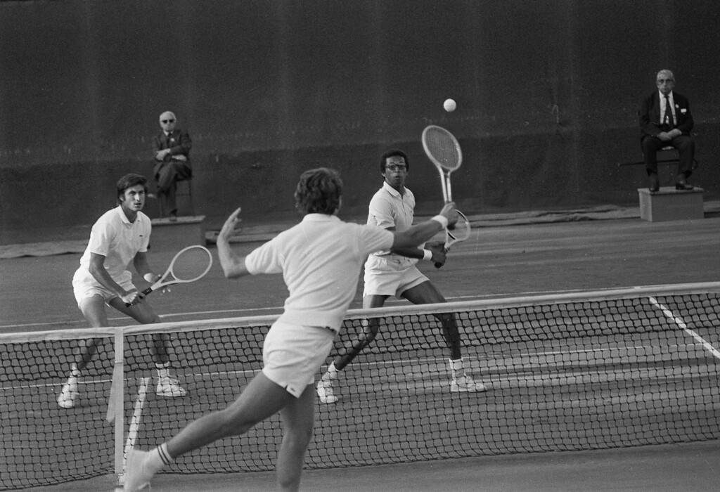 . Arthur Ashe of Richmond, Va., right, gets ready to return the ball hit by Australia\'s Ray Ruffels, back to camera, during doubles match in the French Open at Roland Garros Stadium near Paris, June 1, 1970.  Ashe and his partner Charles Pasarell, left, of Santurce, Puerto Rico, defeated Ruffels and his partner, Ray Keldie, also of Australia.  (AP Photo)