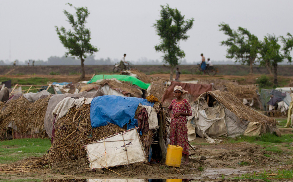. An internally displaced Rohingya woman stands outside her tent at a camp for displaced Rohingya in Sittwe, northwestern Rakhine State, Myanmar, ahead of the arrival of Cyclone Mahasen, Wednesday, May 15, 2013. A massive evacuation to clear low-lying camps ahead of the cyclone has run into a potentially deadly snag as members of the displaced Rohingya minority living there have refused to leave because they don\'t trust Myanmar authorities. (AP Photo/Gemunu Amarasinghe)