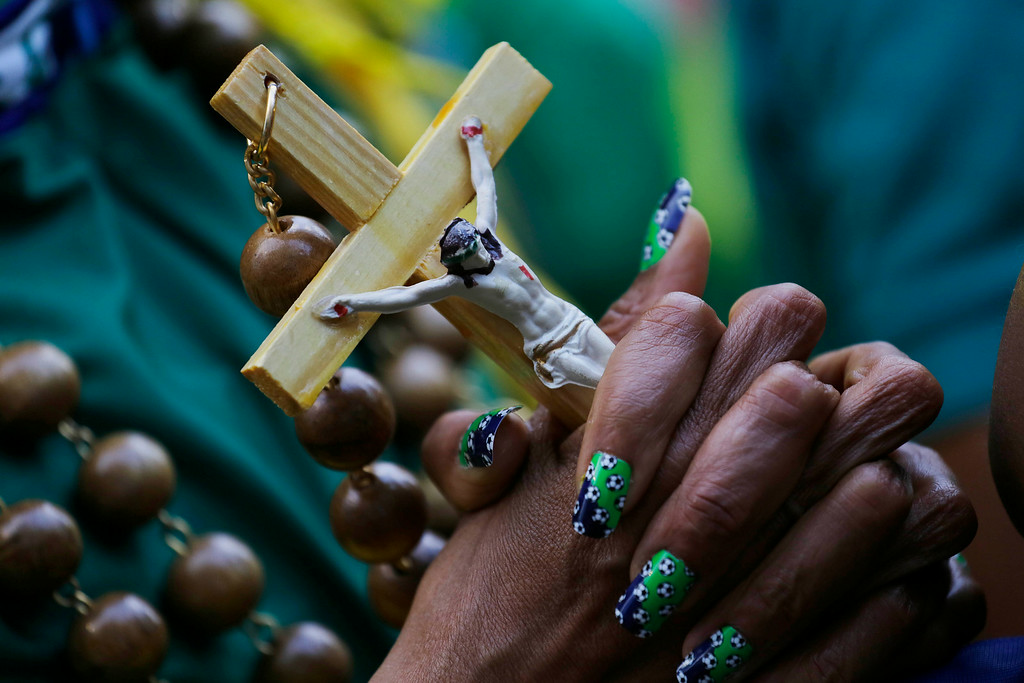 . A Brazil soccer fan whose fingernails are decorated with soccer ball decals, holds a crucifix as she watches the World Cup quarterfinal match between Brazil and Colombia inside the FIFA Fan Fest area in Sao Paulo, Brazil, Friday, July 4, 2014. (AP Photo/Nelson Antoine)