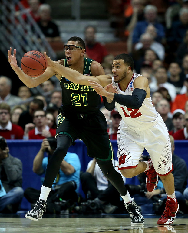 . Isaiah Austin #21 of the Baylor Bears and Traevon Jackson #12 of the Wisconsin Badgers go after the ball in the first half during the regional semifinal of the 2014 NCAA Men\'s Basketball Tournament at the Honda Center on March 27, 2014 in Anaheim, California.  (Photo by Jeff Gross/Getty Images)