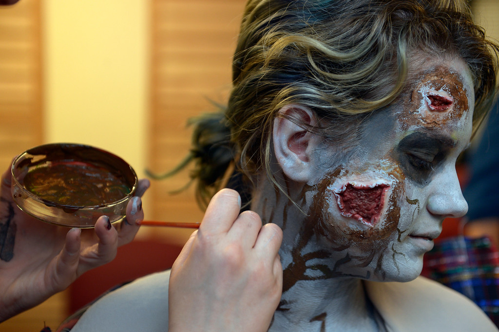 """. BOULDER, CO- FEBRUARY 19:  Danica Minor, a make-up artist with Theatrical Costumes Etc, applies \""""Zombie\"""" make up to zombie Phillipa Keosheyan 14.   With the help of a professional videographer, Fairview High School students produced a zombie video to advertise an Awareness Drive in Boulder Valley schools designed to bring attention to a variety of mental health and wellness issues.  Students were made to look like zombies by make-up artists from Theatrical Costumes, Etc. (Photo By Helen H. Richardson/ The Denver Post)"""