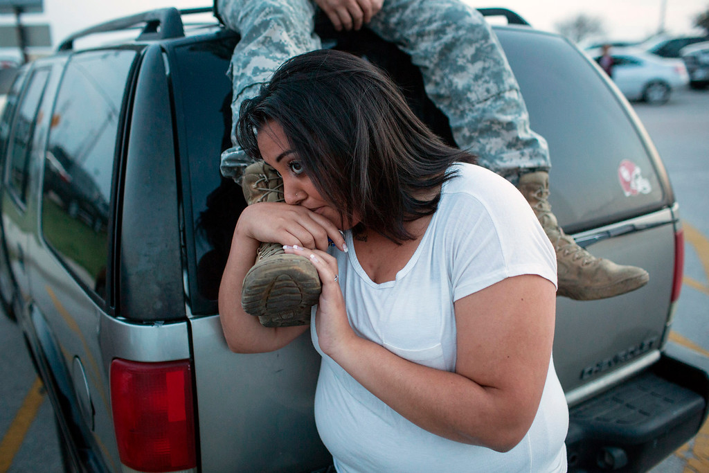 . Lucy Hamlin and her husband, Spc. Timothy Hamlin, wait for permission to re-enter the Fort Hood military base, where they live, following a shooting on the base, Wednesday, April 2, 2014, in Fort Hood, Texas. (AP Photo/ Tamir Kalifa, File)