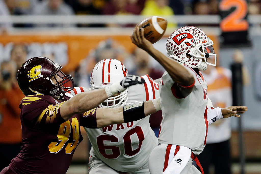 . Central Michigan defensive end Caesar Rodriguez (99) closes in on Western Kentucky quarterback Kawaun Jakes (6) during the second quarter of the Little Caesars Pizza Bowl NCAA college football game at Ford Field in Detroit, Wednesday, Dec. 26, 2012. (AP Photo/Carlos Osorio)