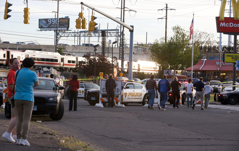 . Onlookers gather at the scene of a collision of two commuter trains in Bridgeport, Connecticut May 17, 2013. Some 20 to 25 people were injured on Friday when two trains collided on a commuter line near Fairfield, Connecticut, but there were no reports of fatalities, police and transit authorities said on Friday. The accident occurred when an eastbound train on the Metro North Railroad derailed and collided with a westbound train near Fairfield, said Metropolitan Transit Authority spokesman Aaron Donovan. REUTERS/ Michelle McLoughlin