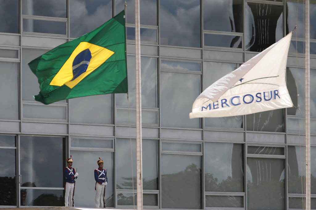 . The Brazilian national flag along with a MERCOSUR banner fly at half-staff to honor plane crash victims, outside the Planalto Presidential Palace in Brasilia, Brazil, Tuesday, Nov. 29, 2016.  A chartered plane carrying a Brazilian soccer team to the biggest match of its history crashed into a Colombian hillside and broke into pieces, killing 75 people and leaving six survivors, Colombian officials said Tuesday. The Brazilian government declared three days of mourning. (AP Photo/Eraldo Peres)