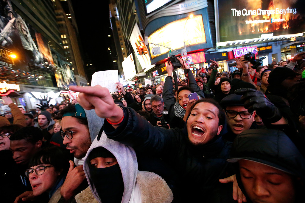 . Protesters rallying against a grand jury\'s decision not to indict the police officer involved in the death of Eric Garner confront police as they attempt to block traffic at the intersection of 42nd Street and Seventh Avenue near Times Square, Thursday, Dec. 4, 2014, in New York. (AP Photo/Jason DeCrow)