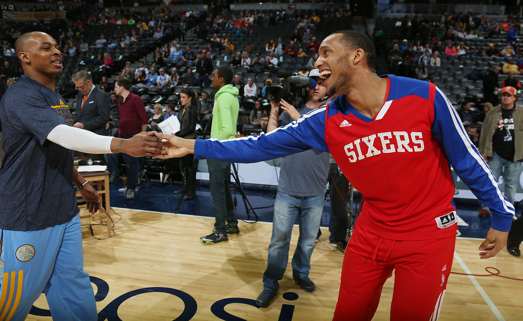 . Philadelphia 76ers guard Evan Turner, right, greets Denver Nuggets guard Randy Foye before an NBA basketball game in Denver on Wednesday, Jan. 1, 2014. (AP Photo/David Zalubowski)