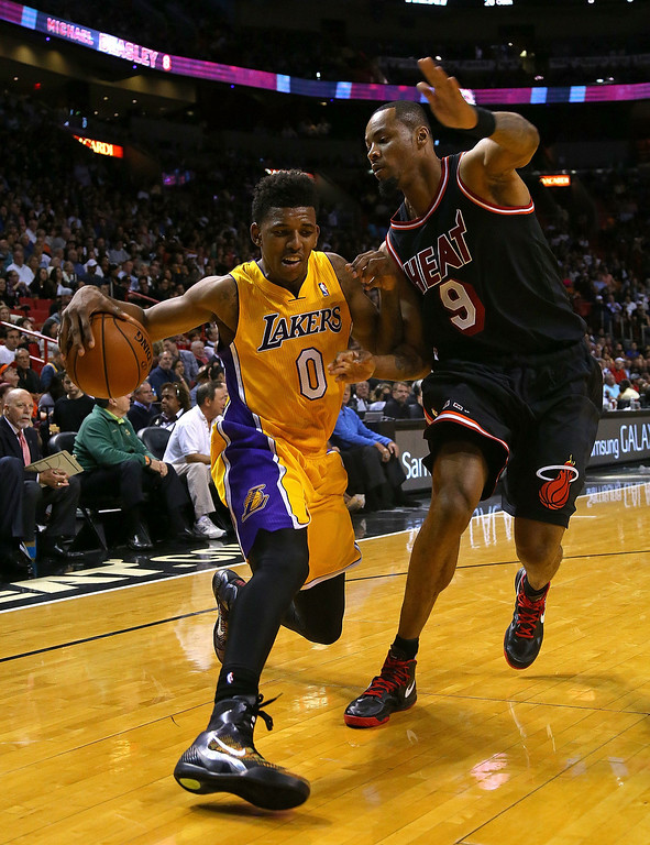 . Nick Young #0 of the Los Angeles Lakers drives on Rashard Lewis #9 of the Miami Heat during a game  at American Airlines Arena on January 23, 2014 in Miami, Florida.  (Photo by Mike Ehrmann/Getty Images)