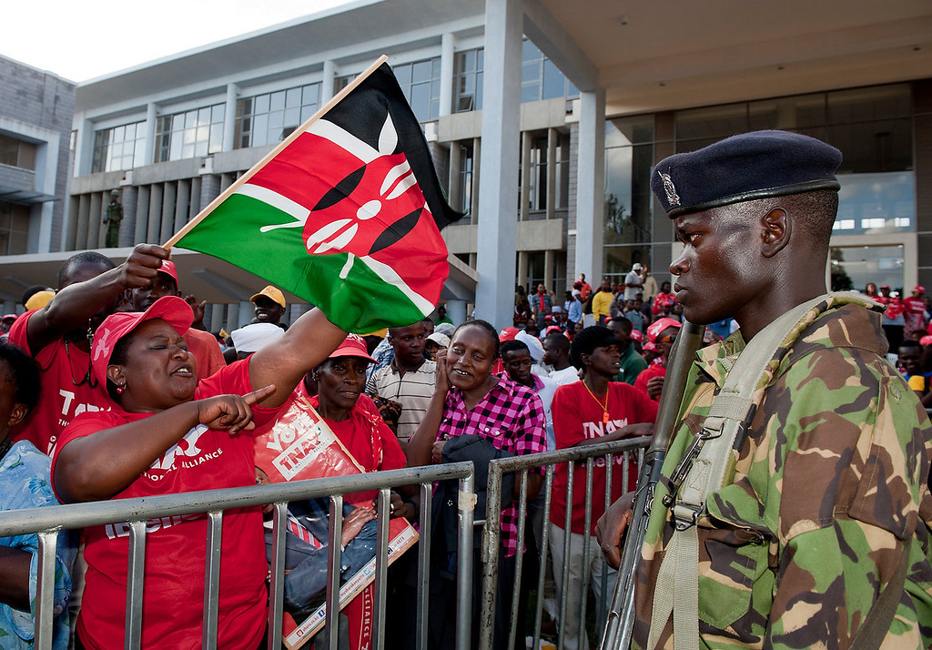 . A Kenyan soldier watches as supporters of Kenyan presidential candidate Uhuru Kenyatta celebrate at the Catholic University where Uhuru Kenyatta gave the acceptance speech of his victory in Kenya\'s national elections on March 9, 2013 in Nairobi.  AFP PHOTO /  Jennifer Huxta/AFP/Getty Images