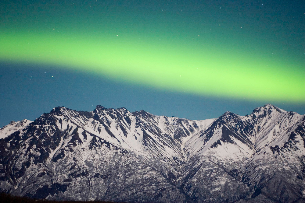 Description of . A band of Aurora Borealis, the Northern Lights,  stretches over the Chugach Range near Palmer, Alaska in this February file photo. Scientists think they have discovered the energy source of the spectacular color displays seen in the northern lights. (AP  Photo/Bob Martinson, FILE)