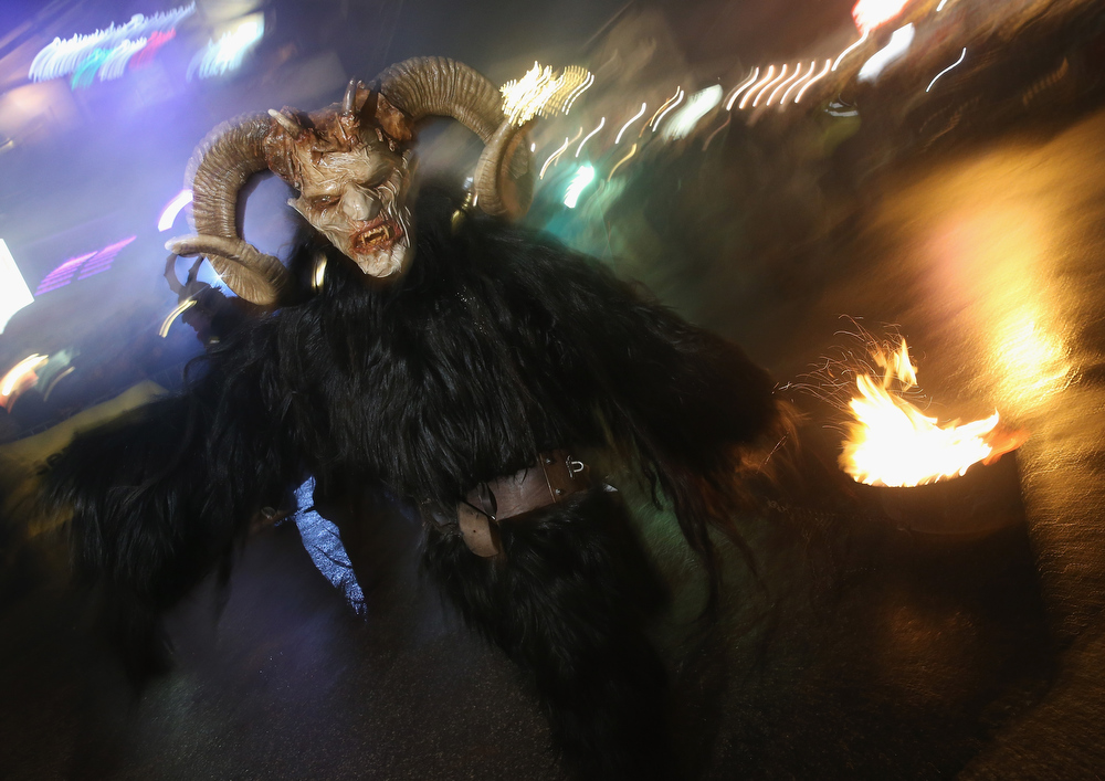 . A participant dressed as the Krampus creature walks the streets in search of delinquent children during Krampus night on November 30, 2013 in Neustift im Stubaital, Austria. Sixteen Krampus groups including over 200 Krampuses participated in the first annual Neustift event. Krampus, in Tyrol also called Tuifl, is a demon-like creature represented by a fearsome, hand-carved wooden mask with animal horns, a suit made from sheep or goat skin and large cow bells attached to the waist that the wearer rings by running or shaking his hips up and down. Krampus has been a part of Central European, alpine folklore going back at least a millennium, and since the 17th-century Krampus traditionally accompanies St. Nicholas and angels on the evening of December 5 to visit households to reward children that have been good while reprimanding those who have not. However, in the last few decades Tyrol in particular has seen the founding of numerous village Krampus associations with up to 100 members each and who parade without St. Nicholas at Krampus events throughout November and early December.  (Photo by Sean Gallup/Getty Images)