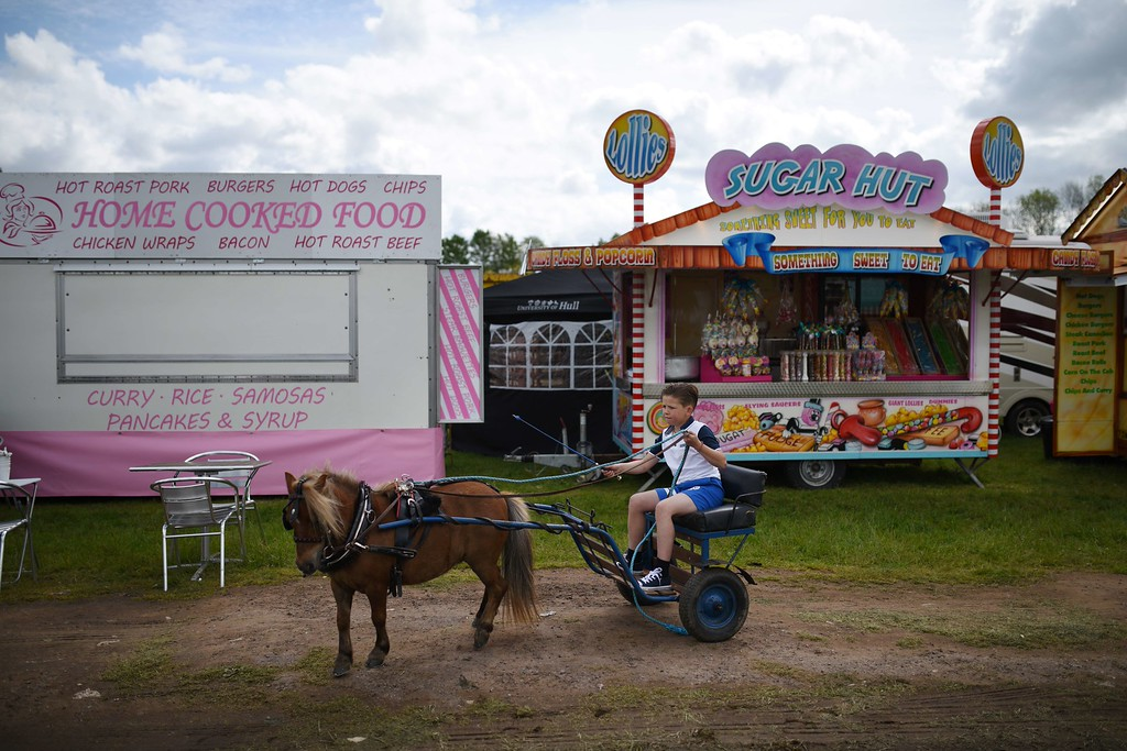 . A boy young rides a miniature horse-drawn carriage through food stalls on the opening day of the annual Appleby Horse Fair, in the town of Appleby-in-Westmorland, North West England on June 4, 2015. The annual event attracts thousands of travelers from across Britain to gather and buy and sell horses. AFP PHOTO / OLI SCARFF/AFP/Getty Images