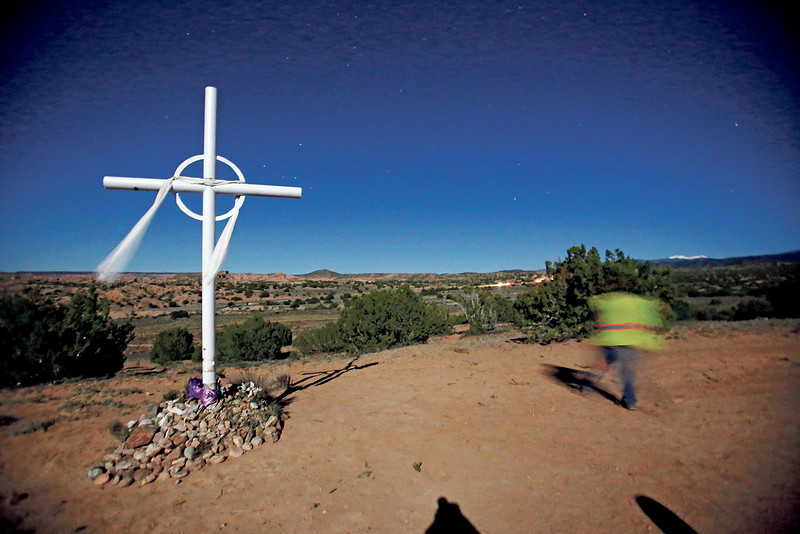 A pilgrim walks by one of the crosses on the way to the Santuario de Chimayo on Good Friday, April 19, 2019. Luis Sánchez Saturno/The New Mexican