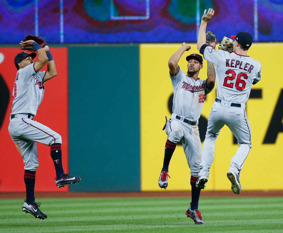 . Minnesota Twins\' Eddie Rosario, left, Byron Buxton, center, and Max Kepler celebrate an 8-6 victory over the Cleveland Indians in a baseball game, Tuesday, Sept. 26, 2017, in Cleveland. (AP Photo/Ron Schwane)