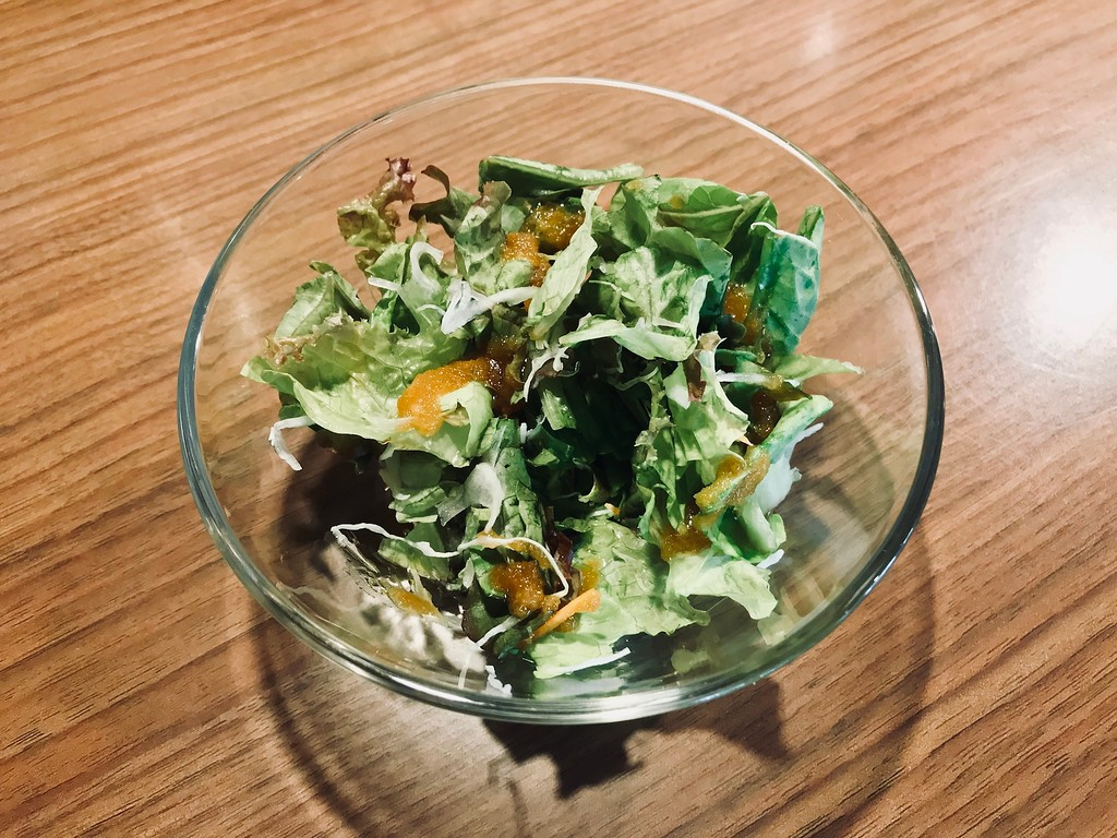 Free small salad with an onion-heavy dressing served at lunch.