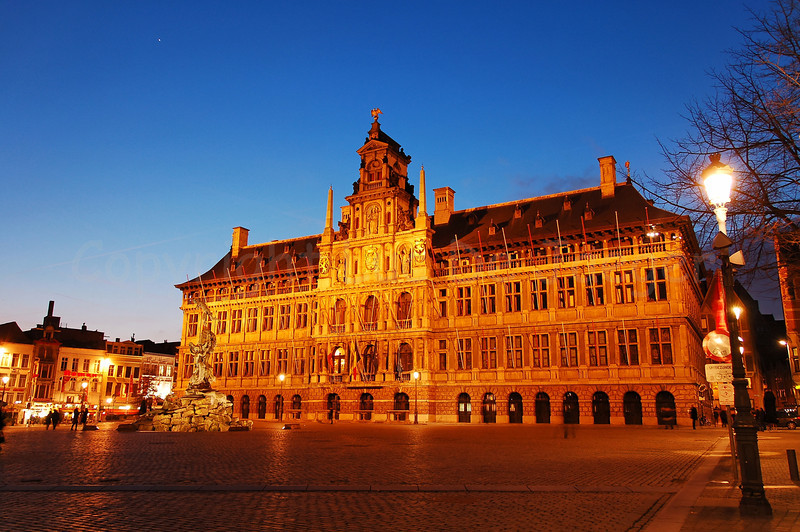 The Market square and the Town Hall of Antwerp (Antwerpen), Belgium captured at dusk. In front of the Town Hall is the bronze statue of Silvius Brabo.