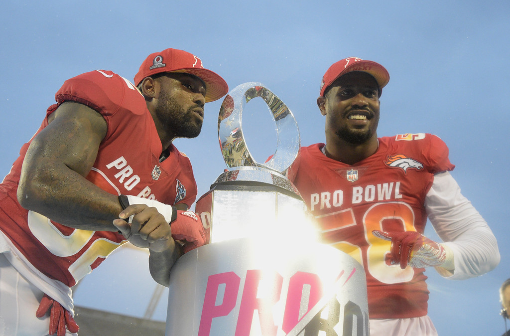 . AFC linebacker Von Miller (58), of the Denver Broncos and tight end Delanie Walker (82), of the Tennessee Titans, pose with the NFL Pro Bowl trophy after defeating the AFC 24-23, in Orlando, Fla., Sunday, Jan. 28, 2018. (AP Photo/Phelan M. Ebenhack)