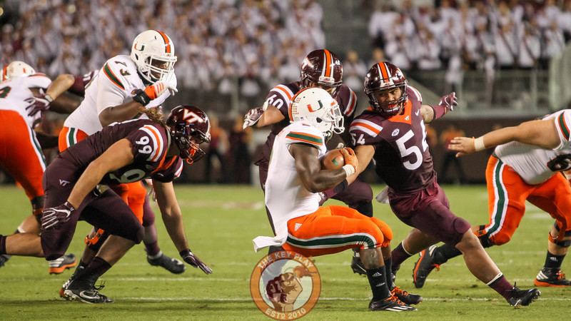 Andrew Motuapuaka (54) and Vinny Mihota (99) chase down Miami's Joseph Yearby. (Mark Umansky/TheKeyPlay.com)