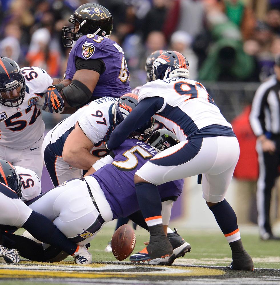 . Denver Broncos defensive tackle Justin Bannan (97) forces a fumble by Baltimore Ravens quarterback Joe Flacco (5) during the first quarter Sunday, December 16, 2012 at M&T Bank Stadium. John Leyba, The Denver Post