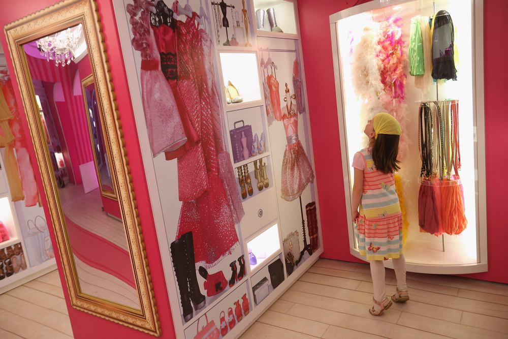 . Amalie, 7, looks at items in Barbie wardrobe while visiting the Barbie Dreamhouse Experience on May 16, 2013 in Berlin, Germany. The Barbie Dreamhouse is a life-sized house full of Barbie fashion, furniture and accessories and will be open to the public until August 25 before it moves on to other cities in Europe.  (Photo by Sean Gallup/Getty Images)