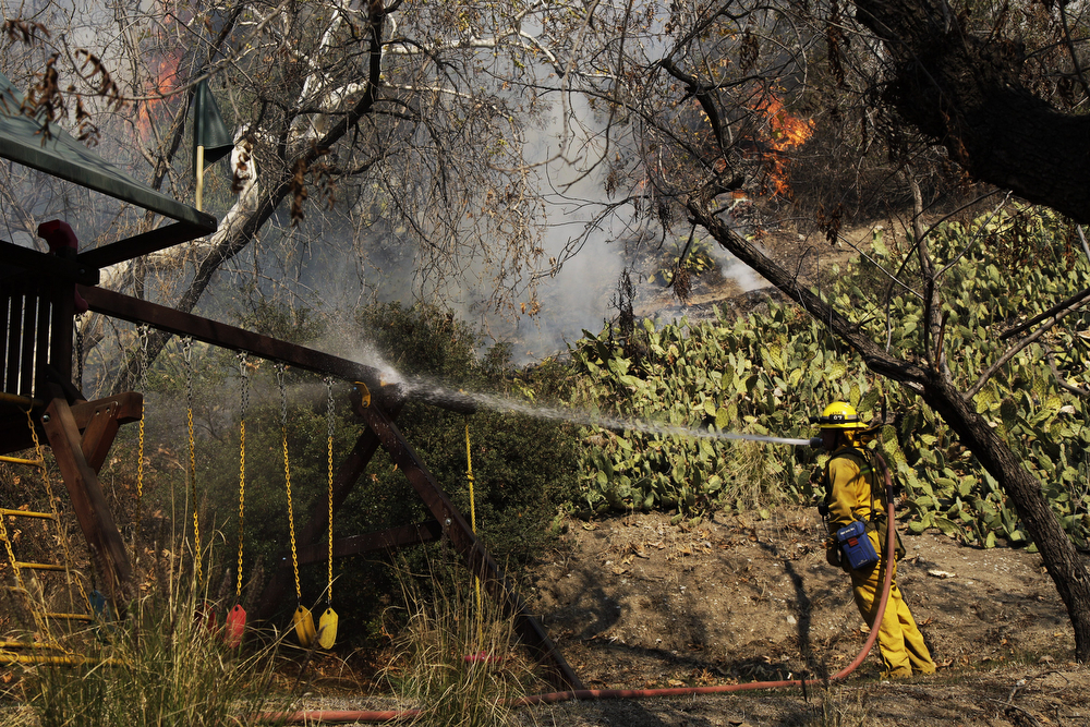 . Firefighter Jason Mendoza helps extinguish the wildfires as they near the house of Michael Allawos on Highcrest Rd. on January 16, 2014 in Glendora, California. A wildfire near Glendora in the San Gabriel Valley has prompted officials to order evacuations for houses near the fire.  (Photo by Dan R. Krauss/Getty Images)