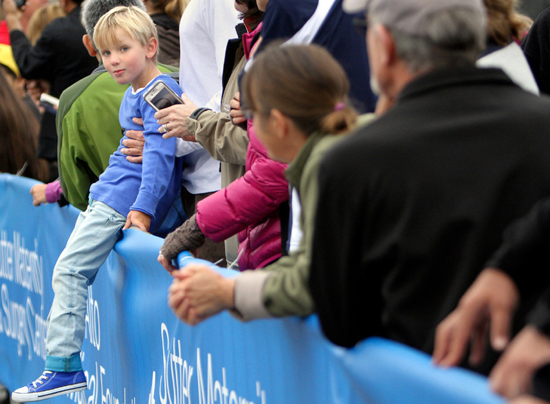 . Hudson Ward, 5, joins hundreds of spectators as he sits on a barrier along Opal Cliff Drive in Capitola on Sunday morning during the 2013 Wharf to Wharf race. (Kevin Johnson/Sentinel)