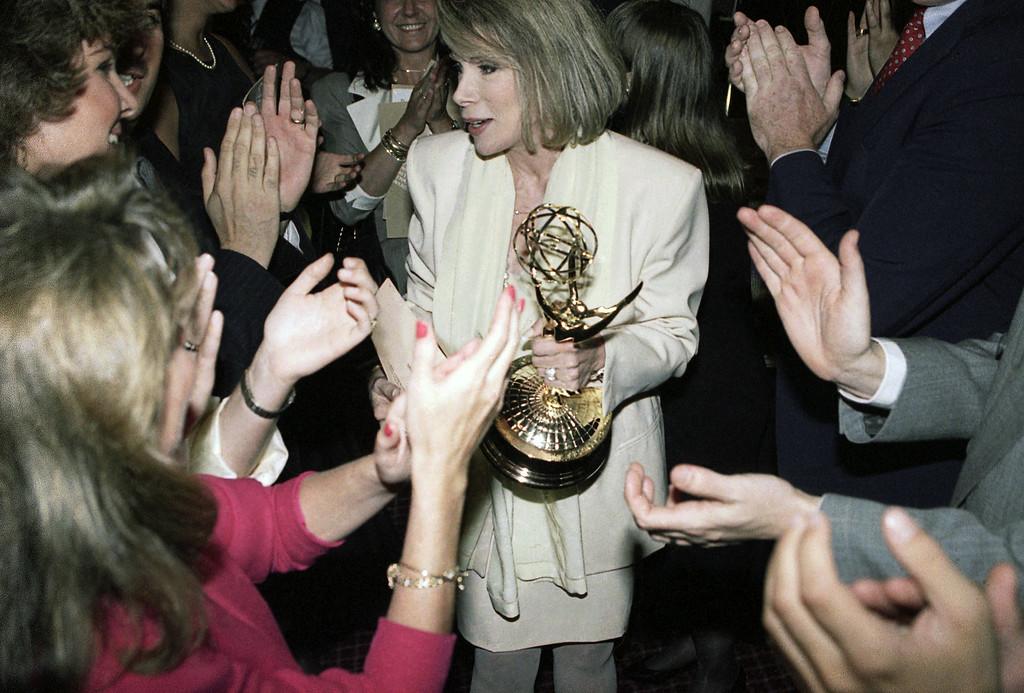 ". Talk show host Joan Rivers is applauded by fans after winning her first Emmy as best talks show host in New York on Thursday, June 28, 1990. Rivers, host of the syndicated \""The Joan Rivers Show,\"" dedicated her Emmy to her late husband, Edgar Rosenberg. (AP Photo/Marty Lederhandler)"