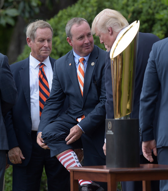 . Rep. Jeff Duncan, R-S.C. center, lifts his pant leg to show off his stripped socks to President Donald Trump during a ceremony on the South Lawn of the White House in Washington, Monday, June 12, 2017, honoring the 2016 NCAA Football National Champions Clemson University Tigers. Rep. Joe Wilson, R-S.C. is at left. (AP Photo/Susan Walsh)