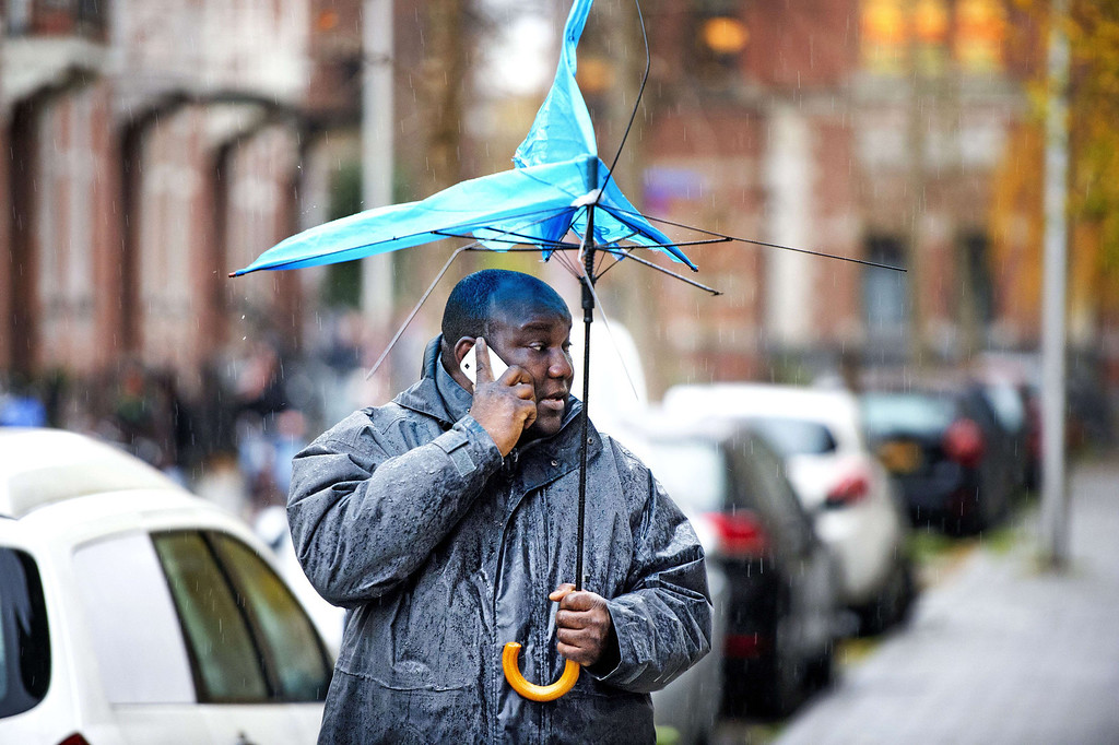". A man using his cellular phone walks while holding a broken umbrella on December 5, 2013 in Utrecht, The Netherlands. As forecasters sounded a ""code orange\"" extreme weather warning, The Netherlands is preparing for heavy storms with surging tides and winds predicted to gust up to 130 km/h (81 miles per hour) in places in the north. AFP PHOTO / ANP / ROBIN UTRECHT  *"