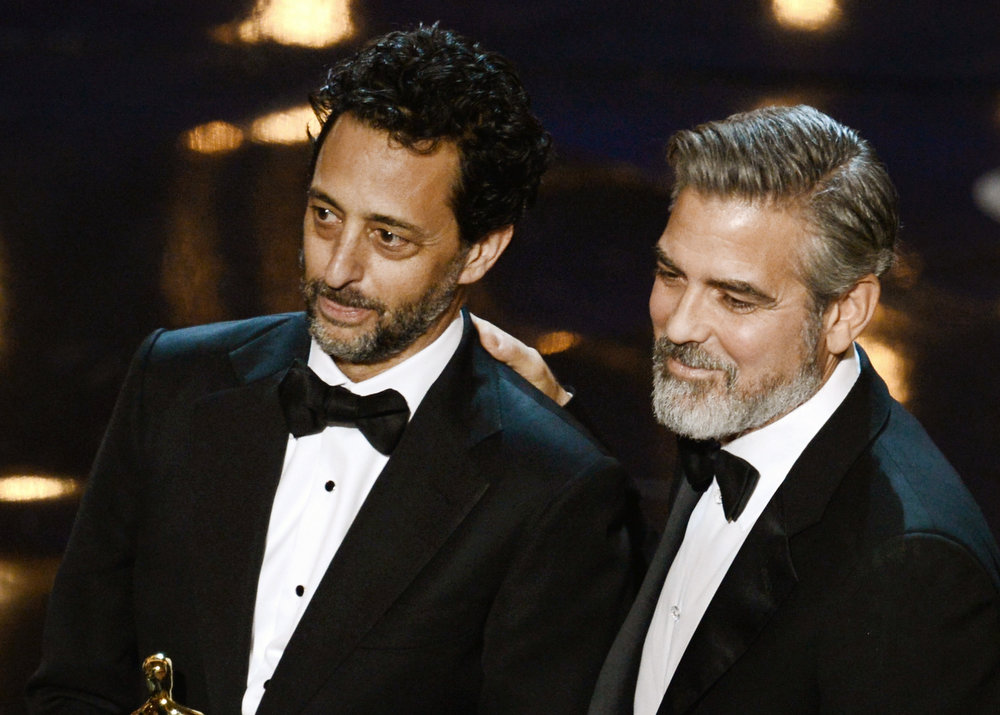 "Description of . Producer Grant Heslov and producer George Clooney accept the Best Picture award for ""Argo"" along with members of the cast and crew onstage during the Oscars held at the Dolby Theatre on February 24, 2013 in Hollywood, California.  (Photo by Kevin Winter/Getty Images)"