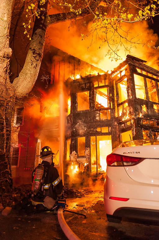 . A Gardner firefighter puts water into a fully involved house on Woodland Ave at the outset of a 3rd Alarm fire. SENTINEL&ENTERPRISE/ Jim Marabello