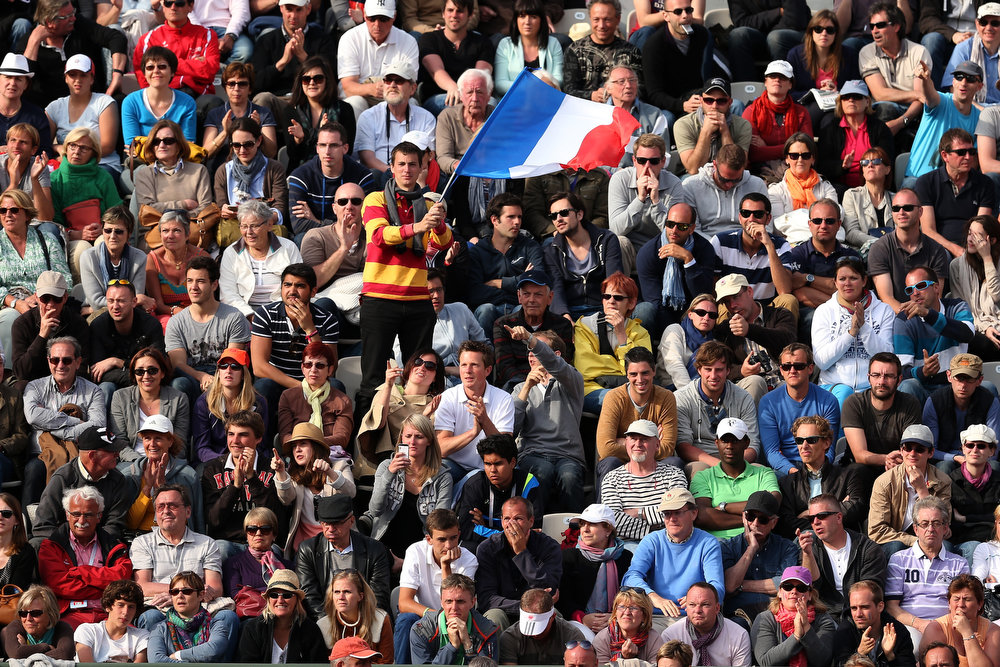 . A tennis fan waves thre French national flag in the crowd during the Men\'s Singles match between Stanislas Wawrinka of Switzerland and Richard Gasquet of France during day nine of the French Open at Roland Garros on June 3, 2013 in Paris, France.  (Photo by Clive Brunskill/Getty Images)