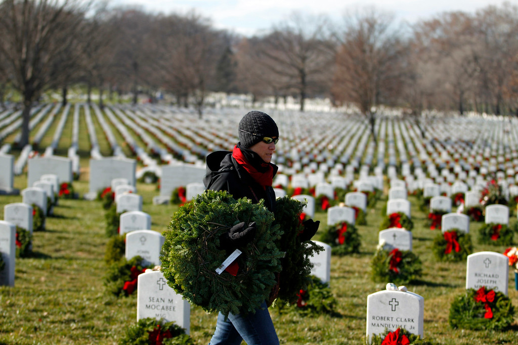 . Volunteers helps to lay holiday wreaths at the graves at Arlington National Cemetery in Arlington, Va., on Saturday Dec. 15, 2012, during Wreaths Across America Day. Wreaths Across America was started in 1992 at Arlington National Cemetery by Maine businessman Morrill Worcester and has expanded to hundreds of veterans\' cemeteries and other locations in all 50 states and beyond. (AP Photo/Jose Luis Magana)