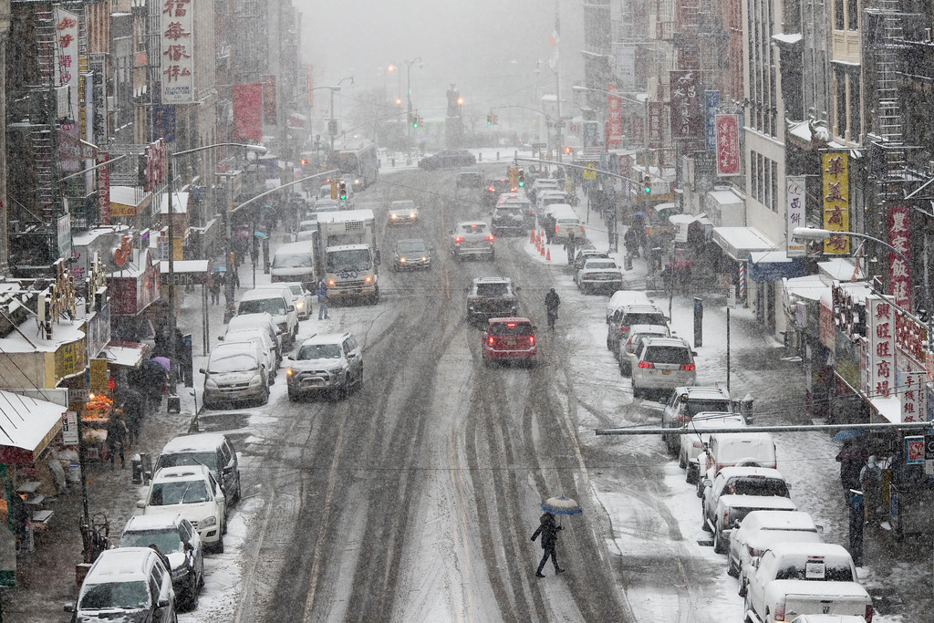 . Snow falls on pedestrians and traffic making their way across East Broadway in Lower Manhattan, Saturday, Jan. 7, 2017. The Weather Service issued a winter weather advisory for New York City and the northern suburbs. Snow began falling from New York City and points east at mid-morning Saturday. (AP Photo/Mary Altaffer)