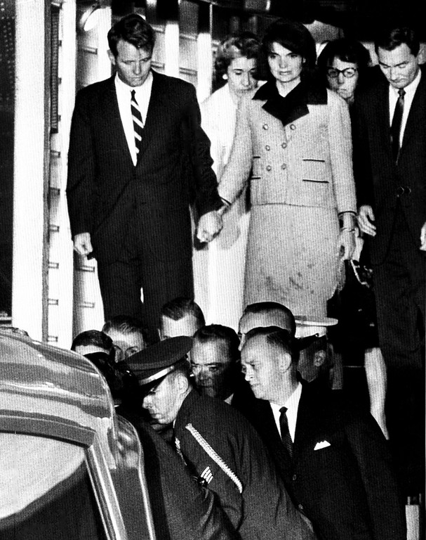 . Jacqueline Kennedy with bloodstains on her clothes stands next to Robert Kennedy as Kennedy\'s coffin (not visible) is placed in an ambulance after arriving at Edwards Air Force base Nov. 22, 1963. Associated Press file