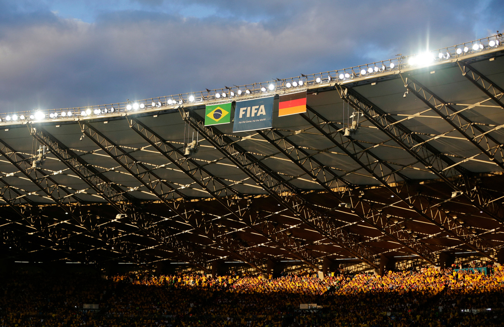 Description of . Sunlight shines down on a group of spectators during the World Cup semifinal soccer match between Brazil and Germany at the Mineirao Stadium in Belo Horizonte, Brazil, Tuesday, July 8, 2014. (AP Photo/Matthias Schrader)