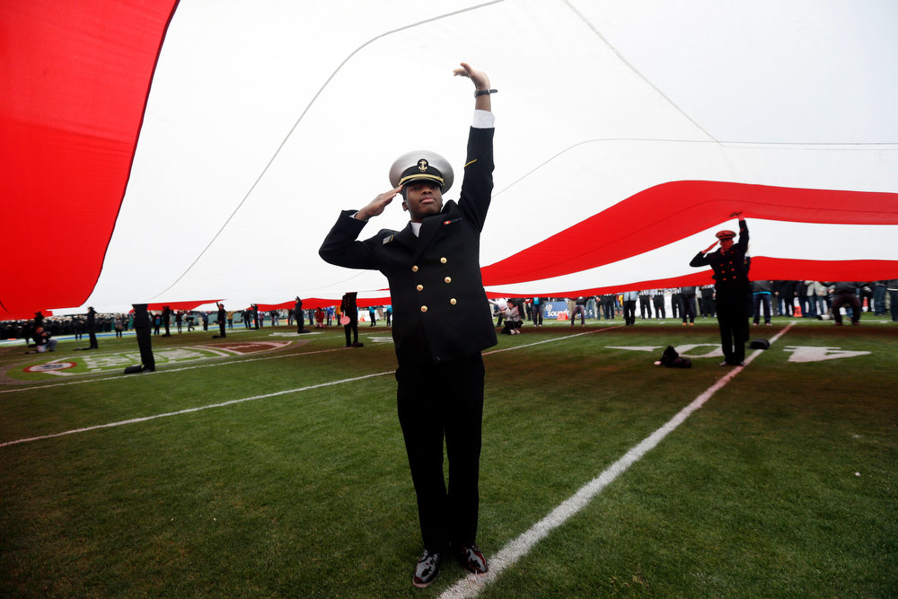 Description of . A United States Naval Academy cadet salutes while holding the U.S. flag before the Fight Hunger Bowl NCAA college football game between Navy and Arizona State in San Francisco, Saturday, Dec. 29, 2012. (AP Photo/Marcio Jose Sanchez)