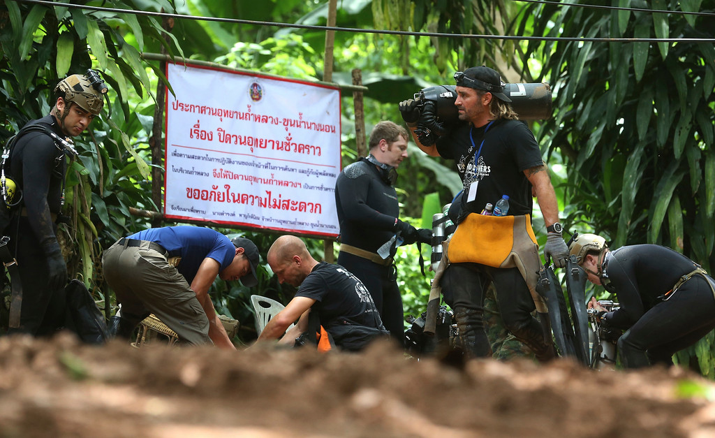 ". International rescuers team prepare to enter the cave where a young soccer team and their coach trapped by flood waters Thursday, July 5, 2018, in Mae Sai, Chiang Rai province, in northern Thailand. With more rain coming, Thai rescuers are racing against time to pump out water from a flooded cave before they can extract 12 boys and their soccer coach with minimum risk, officials said Thursday. The sign reads: ""cave is closed.\"" (AP Photo/Sakchai Lalit)"