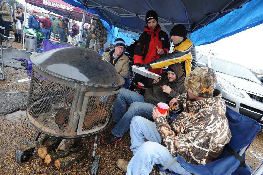 Description of . Louisiana-Monroe fancs, from left,  Jeff Justus, Kevin Nolton, Garrett Tiller, Kyle Deemer and Mark Lafdahl enjoy a warm fire and food while while tailgating before the Independence Bowl NCAA college football game between Louisiana-Monroe and Ohio in Shreveport, La., Friday, Dec. 28, 2012. (AP Photo/The Shreveport Times, Douglas Collier)