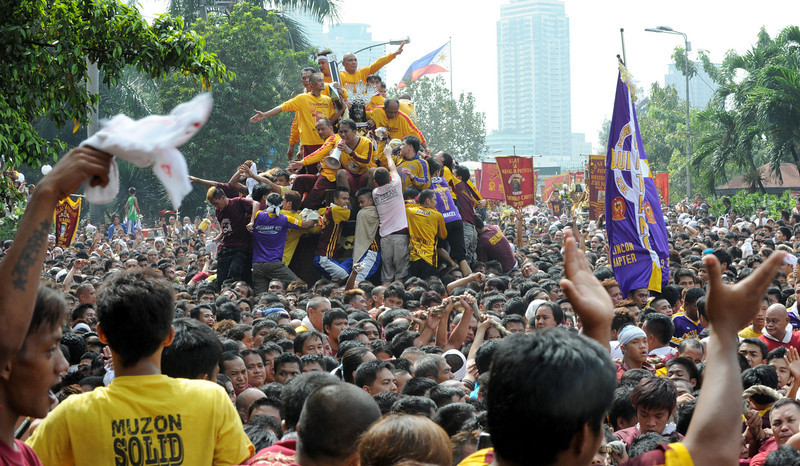 . Catholic devotees jostle for positions as they try to kiss the cross (top C) draped on the statue of Black Nazarene during the annual procession in honor of the centuries-old icon of Jesus Christ in Manila on January 9, 2013. Masses of Catholic devotees swept through the Philippine capital on January 9 in a spectacular outpouring of passion for a centuries-old icon of Jesus Christ that many believe can perform miracles.  JAY DIRECTO/AFP/Getty Images