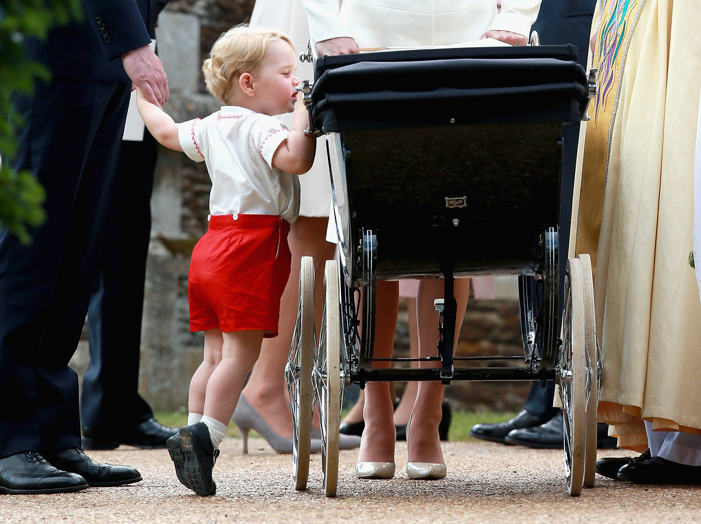 . Prince George of Cambridge looks at his sister Princess Charlotte of Cambridge in her pram as he leaves the Church of St Mary Magdalene on the Sandringham Estate for the Christening of Princess Charlotte of Cambridge on July 5, 2015 in King\'s Lynn, England.  (Photo by Chris Jackson/Getty Images)