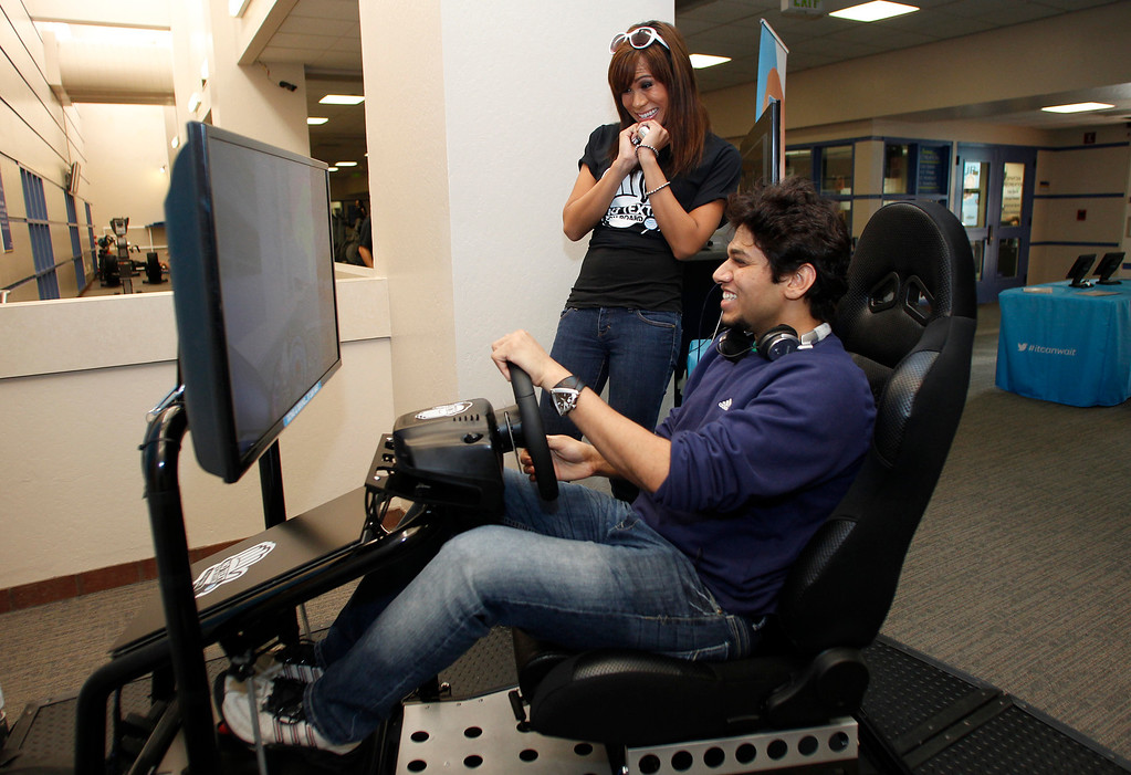 . As Liana Estillore, 23, of Cupertino, watches, Omkar Deo, 24, of Campbell, tries to text while driving a simulator at San Jose State University on Friday, Jan. 25, 2013. San Jose State hosted a Texting-while-driving simulator to raise awareness among students regarding the dangers of texting while driving. (Jim Gensheimer/Staff)