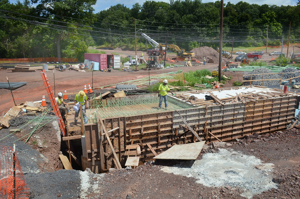 . Men work at the Godshall Road, Cowpath Road, West Broad Street intersection in Franconsia Township that is undergoing reconstruction for an expected reopening in November.   At center is  a box culvert that will carry a tributary of the Skippack Creek under the roadway.    Monday,  August 4, 2014.   Photo by Geoff Patton