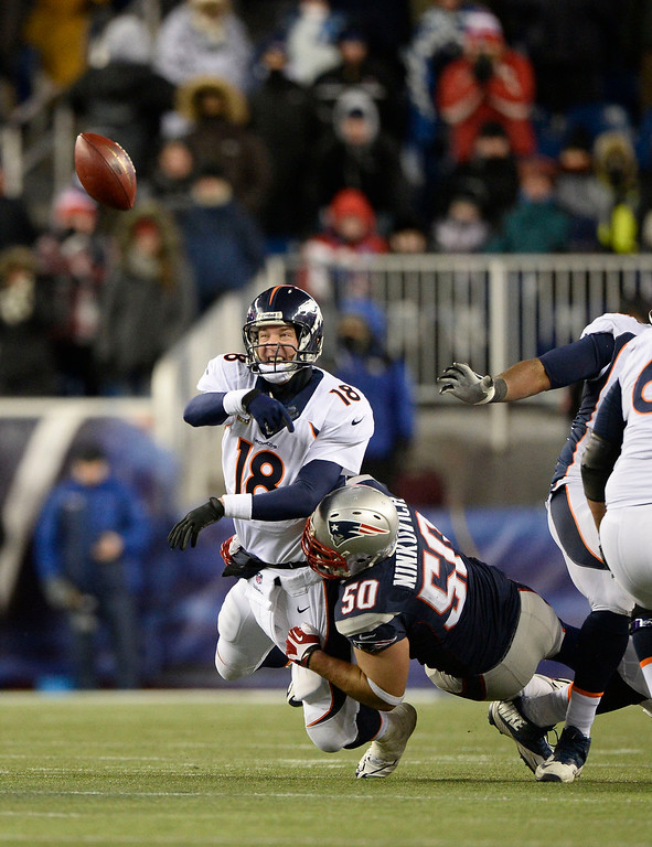 . Denver Broncos quarterback Peyton Manning (18) is forced to throw a pass under pressure by New England Patriots defensive end Rob Ninkovich (50) during overtime November 24, 2013 at Gillette Stadium. (Photo by John Leyba/The Denver Post)